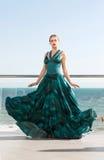 Очаровательная девушка в длинном темном ом-зелен платье на предпосылке моря Женщина в длинном пропуская зеленом платье около моря Стоковые Фото