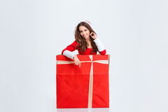Очаровательная девушка в костюме Санта Клауса сидя внутри подарочной коробки Стоковое фото RF