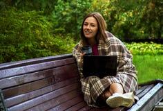 Очаровательная девушка обернутая в одеяле сидя на стенде в равенстве стоковое изображение