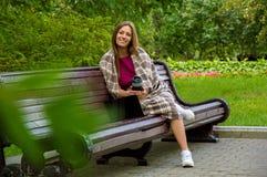 Очаровательная девушка обернутая в одеяле сидя на стенде в равенстве Стоковое Изображение RF