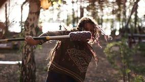 Очаровательная девушка при dreadlocks вертясь ручка в лесе лета видеоматериал