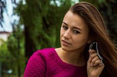 Очаровательная девушка сидит в парке и слушать к часам Стоковые Изображения