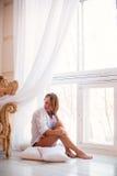 Очаровательная девушка сидя на windowsill Стоковое фото RF