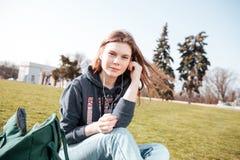 Очаровательная женщина в наушниках слушая к музыке на лужайке Стоковое Фото