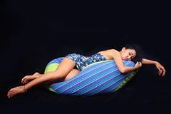 Очаровательная женщина в флористическом голубом платье представляя ослабленный лежать на сумке фасоли на черной предпосылке Стоковые Фотографии RF