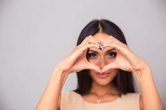 Очаровательная женщина делая сердце с пальцами Стоковые Изображения RF