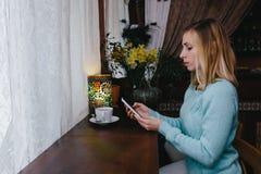 Очаровательная женщина с красивыми хорошими новостями чтения улыбки на черни Стоковая Фотография