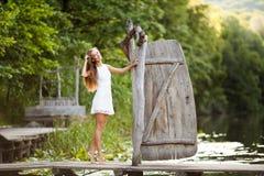 Очаровательная длинн-с волосами усмехаясь модель счастливой девушки брюнет привлекательная в белой прогулке платья рекой Стоковое Изображение