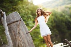 Очаровательная длинн-с волосами усмехаясь модель счастливой девушки брюнет привлекательная в белой прогулке платья рекой Стоковое Фото