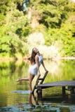 Очаровательная длинн-с волосами усмехаясь модель счастливой девушки брюнет привлекательная в белой прогулке платья рекой Стоковые Изображения RF