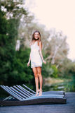 Очаровательная длинн-с волосами усмехаясь модель счастливой девушки брюнет привлекательная в белой прогулке платья рекой Стоковые Изображения