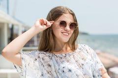 Очаровательная и красивая молодая модельная девушка в стеклах солнца на предпосылке моря Милая женская модель красивейшее солнце  Стоковое Изображение RF