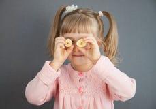 Очаровательная маленькая девочка играя с частями зрелого банана Стоковые Изображения RF