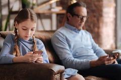 Очаровательная маленькая девочка и дед демонстрируя наркоманию интернета внутри помещения Стоковая Фотография