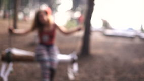 Очаровательная маленькая девочка на качании в лесе и усмехаться лета видеоматериал