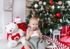 Очаровательная маленькая девочка сидит под рождественской елкой с подарками стоковая фотография
