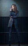 Очаровательная молодая женщина брюнет в черных кожаных обмундировании, пальто и брюках, с темнотой - серой стеной на предпосылке  Стоковые Фото