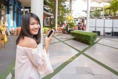 Очаровательная молодая женщина в белой рубашке читают или сообщение текстов к мобильному телефону, против старых домов grunge в г Стоковое Изображение