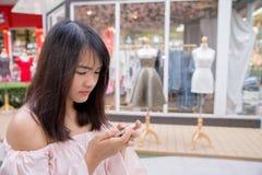 Очаровательная молодая женщина в белой рубашке читают или сообщение текстов к мобильному телефону, против старых домов grunge в г Стоковое Фото
