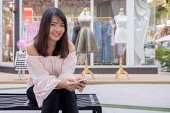 Очаровательная молодая женщина в белой рубашке читают или сообщение текстов к мобильному телефону, против старых домов grunge в г Стоковые Изображения