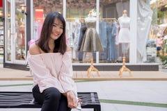 Очаровательная молодая женщина в белой рубашке читают или сообщение текстов к мобильному телефону, против старых домов grunge в г Стоковая Фотография