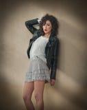 Очаровательная молодая курчавая женщина брюнет в юбке шнурка короткой и черная склонность кожаной куртки против стены Сексуальная Стоковое Изображение RF