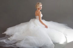 Очаровательная молодая невеста в роскошном платье свадьбы девушки белизна довольно Серая предпосылка вакханические стоковое изображение