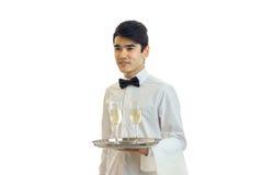 Очаровательная молодая рубашка ` s кельнера смотрит в расстояние и держать поднос с 2 стеклами вина Стоковое Изображение