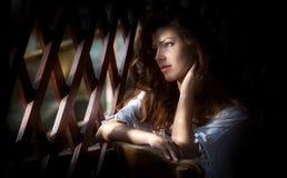 Очаровательная молодая русая женщина волос смотря через деревянную решетку Сексуальная шикарная молодая женщина при длинное вьющи Стоковые Фотографии RF