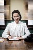 Очаровательное винтажное работник службы рисепшн работая на столе офиса Стоковые Изображения
