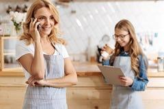 Очаровательное предприниматель кафе-бара обсуждая работу на телефоне Стоковые Фото