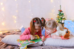 Очаровательные маленькие девочки играют совместно и беседуют, лежащ на поле и Стоковые Фотографии RF
