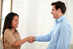 Очаровательные пары сотрудников давая руки приветствуя стоковое изображение