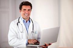 Очаровательный взрослый доктор используя его компьтер-книжку Стоковое Фото