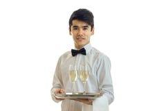 Очаровательный кельнер в белой рубашке держа поднос с стеклами спирта Стоковые Изображения RF