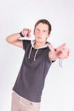 Очаровательный красивый молодой человек в formalwear держит его руки, пункты с пальцами на камере пока стоящ белая предпосылка Стоковые Фотографии RF