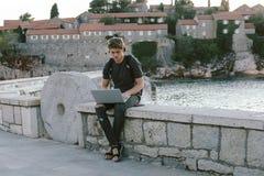 Очаровательный молодой человек работая на компьтер-книжке около моря, независимом wor Стоковые Фотографии RF