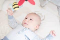 Очаровательный младенец играя при игрушка лежа дальше назад стоковые изображения