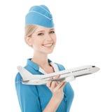 Очаровательный Stewardess держа самолет в руке. Изолированный стоковая фотография