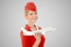 Очаровательный Stewardess держа самолет в руке Серая предпосылка стоковая фотография