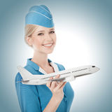 Очаровательный Stewardess держа самолет в руке. стоковое изображение rf