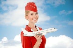Очаровательный Stewardess держа самолет в руке стоковое фото rf