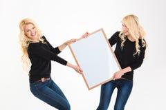 2 очаровывая белокурых близнеца сестер имея потеху держа пустую доску Стоковые Изображения RF