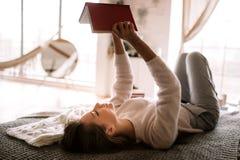 Очаровывая девушка одетая в белых свитере и брюках читает книгу liying на кровати с серым одеялом, белыми подушками и a стоковое фото rf
