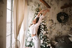 Очаровывая девушка одетая в белых стойках свитера и брюк рядом с деревом Нового Года перед окном и простираниями стоковое изображение rf