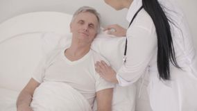 Очаровывая доктор позаботится о неработающий старший человек в кровати акции видеоматериалы