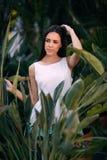 Очаровывая и усмехаясь женщина в белом платье на органическом зеленом цвете выходит предпосылка Милая дама в тропическом лесе Стоковое Изображение RF
