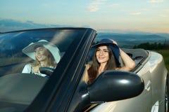 Очаровывая модели управляя роскошным серебряным cabriolete стоковое фото