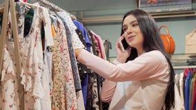 Очаровывая молодая женщина говоря по телефону пока ходящ по магазинам для одежд акции видеоматериалы