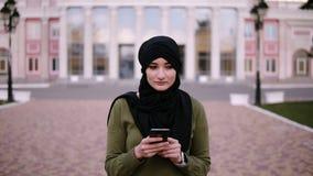 Очаровывая мусульманская женщина в черном hijab печатая по телефону и идя на улицу, идя далеко от здания в предпосылке o акции видеоматериалы